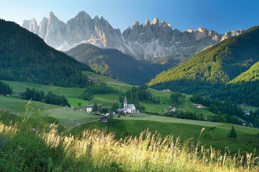 Farmsteads, church and lush meadows in the Val di Funes/Villnöss valley with the Odle/Geislerspitzen Dolomite massif behind | © Magnolia