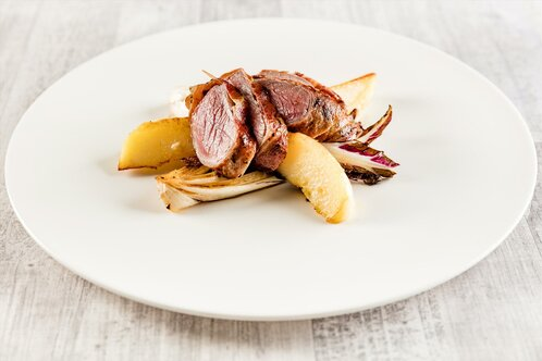 Beef tagliata wrapped in speck over glazed radicchio and baked potatoes